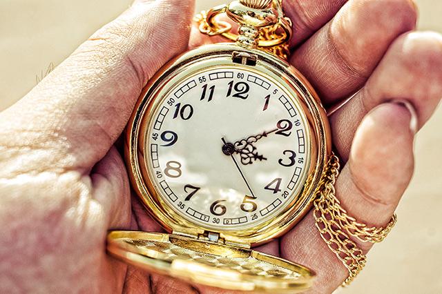 Goldene Taschenuhr in Hand eines alten Mannes